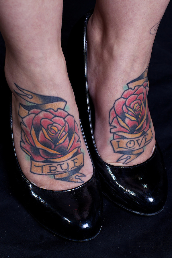 Young danish woman with pinup girl on left shoulder and left lower arm, swallows on left and right front. Two roses on feet with the words True Love.<br />