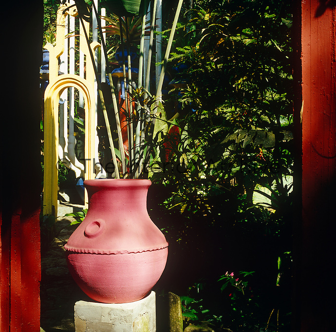 A large terracotta pot has been painted pink and treated as a piece of sculpture against the lush background of the surrounding garden