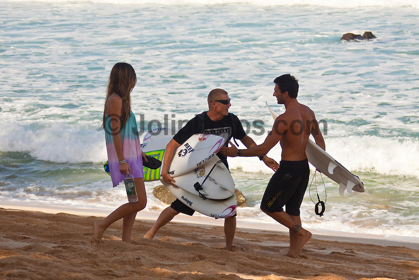 PIPELINE, Oahu/Hawaii (Friday, December 11, 2009) World Title contenders Mick Fanning (AUS) with his wife Karrisa and Joel Parkinson (AUS) meet on the beach at Pipeline and wish each other well. - Round 2 of the Billabong Pipeline Masters, Event No. 10 of 10 on the 2009 ASP World Tour,was completed today in clean four-to-six foot  waves at the Banzai Pipeline...The third and final event in the Vans Triple Crown (an ASP Specialty Series), the Billabong Pipeline Masters plays host to two dramatic story arcs: the showdown for the 2009 ASP World Title and the requalification race for the 2010 ASP Dream Tour. Amidst the world's best surfers exists a spattering of Pipeline specialists, making the competition field particularly challenging to navigate... This event is the last World Championship event of the year and will decide the 2009 World Tilte between Joel Parkinson (AUS) and Mick Fanning (AUS)...The northern hemisphere winter months on the North Shore signal a concentration of surfing activity with some of the best surfers in the world taking advantage of swells originating in the stormy Northern Pacific. Notable North Shore spots include Waimea Bay, Off The Wall, Backdoor, Log Cabins, Rockpiles and Sunset Beach... Ehukai Beach is more  commonly known as Pipeline and is the most notable surfing spot on the North Shore. It is considered a prime spot for competitions due to its close proximity to the beach, giving spectators, judges, and photographers a great view...The North Shore is considered to be one the surfing world's must see locations and every December hosts three competitions, which make up the Triple Crown of Surfing. The three men's competitions are the Reef Hawaiian Pro at Haleiwa, the O'Neill World Cup of Surfing at Sunset Beach, and the Billabong Pipeline Masters. The three women's competitions are the Reef Hawaiian Pro at Haleiwa, the Gidget Pro at Sunset Beach, and the Billabong Pro on the neighboring island of Maui...Photo: Joliphotos.com