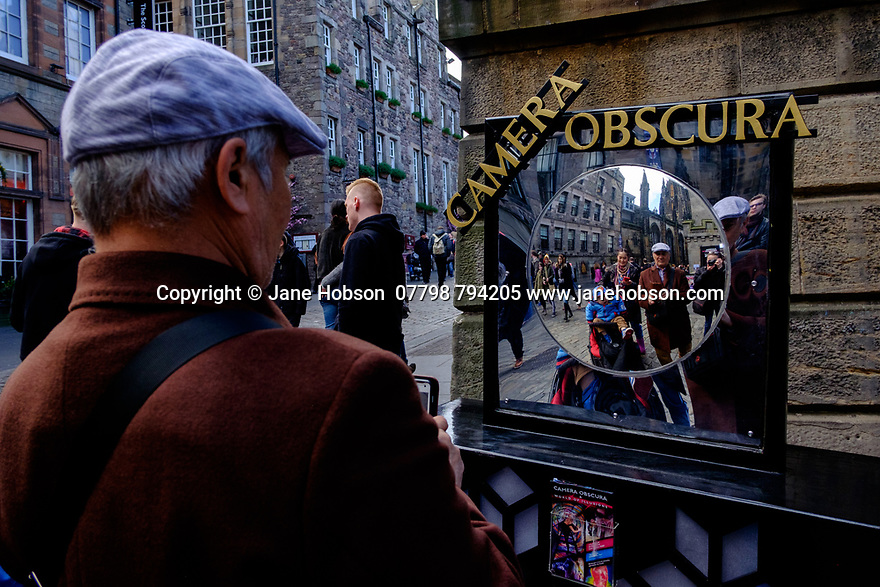 Edinburgh, UK. 15.04.2017. A man takes a selfie, whilst others look on, in a distorting mirror outside the Camera Obscura, on the Royal Mile. Photograph © Jane Hobson.