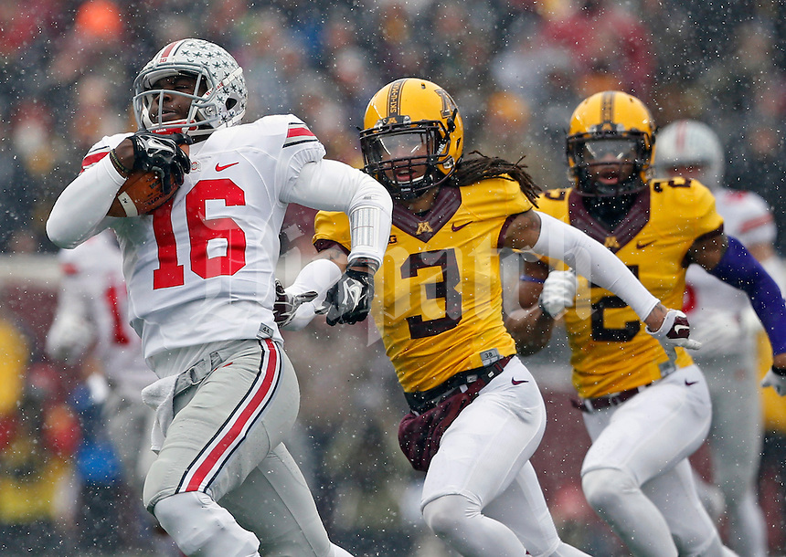 Ohio State Buckeyes quarterback J.T. Barrett (16) scores on a touchdown run against Minnesota Golden Gophers defensive back Derrick Wells (3) during the 1st quarter at TCF Bank Stadium in Minneapolis, Minn. on November 15, 2014.  (Dispatch photo by Kyle Robertson)