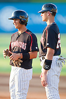 Trayce Thompson #24 (right) of the Kannapolis Intimidators coaches runner Tyler Saladino #1 during a South Atlantic League game against the Lakewood BlueClaws at Fieldcrest Cannon Stadium July 14, 2010, in Kannapolis, North Carolina.  Photo by Brian Westerholt / Four Seam Images