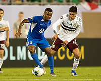 CHARLOTTE, NC - JUNE 23: Edson Alvarez #4 challenges Stephane Abaul #20 during a game between Mexico and Martinique at Bank of America Stadium on June 23, 2019 in Charlotte, North Carolina.