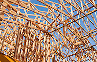 New Residential House Construction with wood framing and roof trusses against a blue sky