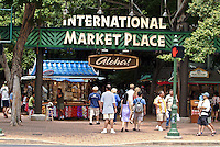 Visitors and a colorful kiosk underneath the banyan tree, sign and entrance to the International Market Place, Waikiki, where shops sell jewelry, aloha wear and other Hawaii souvenirs.