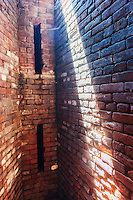 A shaft of sunlight illuminates the brick work in the storage room for gunpowder in the historic Fort Totten Water Battery in Fort Totten in the Bayside neighborhood of Queens in New York on Sunday, June 15, 2014. Construction on the historic fort started in 1862 on Willet's Point overlooking the East River into Long Island Sound.   (© Richard B. Levine)
