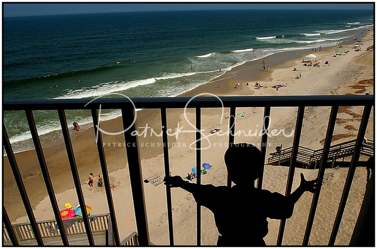 A boy, standing alone, looks down on a beach in the North Carolina Outer Banks. Boy is silhouetted. Model released.