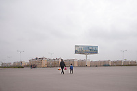 Daytime landscape view of a woman and boy walking in front of a Suburban Building Development in Huinong, China.  © LAN