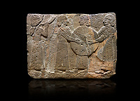 Hittite monumental relief sculpted orthostat stone panel of Procession. Basalt, Karkamıs, (Kargamıs), Carchemish (Karkemish), 900 - 700 B.C. Goddess Kubaba. Anatolian Civilisations Museum, Ankara, Turkey.<br /> <br /> Procession for. There are four figures on the other face of the orthostat. The leftmost figure plays a pipe, while the other three figures play the drums. All of the figures have long skirts and same body heights.  <br /> <br /> Against a black background.
