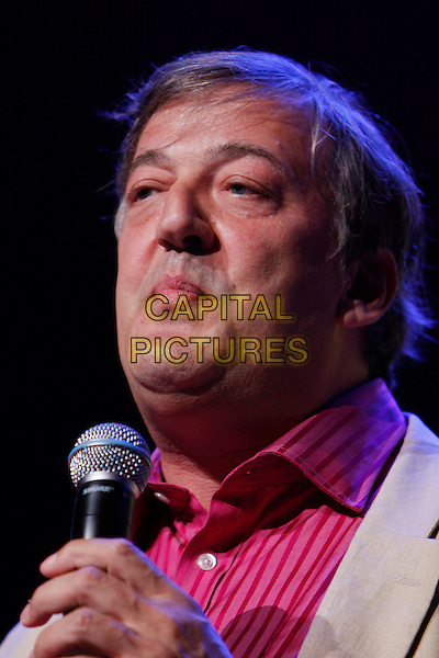 STEPHEN FRY.Performs as part of iTunes Festival 2010 at the Roundhouse, London, England, UK, July 18th 2010..portrait headshot red shirt beige jacket on stage live stand-up show concert gig microphone  yellow funny face .CAP/MAR.© Martin Harris/Capital Pictures.