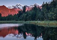 Winter dusk over Aoraki, Mt. Cook and Mt. Tasman of  Southern Alps, reflecting in Lake Matheson, Westland Tai Poutini National Park, West Coast, UNESCO World Heritage Area, South Westland, New Zealand, NZ