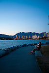 A man takes a break to enjoy the view of the sunset over English Bay and the Burrard Inlet at Kitsalano Beach Park.  Downtown Vancouver and the Mountains are off in the distance.