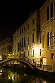 ITALY, Venice.  View of homes and bridge over a canal at night.