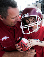 NWA Democrat-Gazette/CHARLIE KAIJO Kenny Jones of Jacksonville (left) holds Colton Jones, 4, before a football game, Saturday, October 6, 2018 at Donald W. Reynolds Razorback Stadium in Fayetteville.
