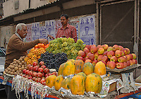 Selecting the best friut to purchase from a fruit cart in Old New Delhi, India.