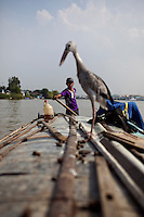 "Tuan, 16, steers the boat while his father fishes on the Hau Giang River, a tributary of the Mekong River, in Chau Doc, in the An Giang Province, Vietnam. When the Mekong River reaches Vietnam it splits into two smaller riveres. The ""Tien Giang"", which means ""upper river"" and the ""Hau Giang"", which means ""lower river"". Photo taken on Monday, December 7, 2009. Kevin German / Luceo Images"