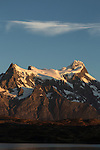 Sunrise view of Cerro Paine Grande taken from Hosteria Pehoe island.  At left on the mountain is Punta Bariloche, then the Central Summit with the Main Summit on the right.    Frequent avalanches come off the thick snow cornices at the edge of the snowfield.  Torres del Paine National Park in Patagonia, Chile.  A UNESCO World Biosphere Reserve.