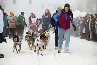 Dog Handlers for Kelley Griffin bring her team down 4rth avenue to the ceremonial start line of the Iditarod sled dog race in downtown Anchorage Saturday, March 2, 2013. ..Photo (C) Jeff Schultz/IditarodPhotos.com  Do not reproduce without permission