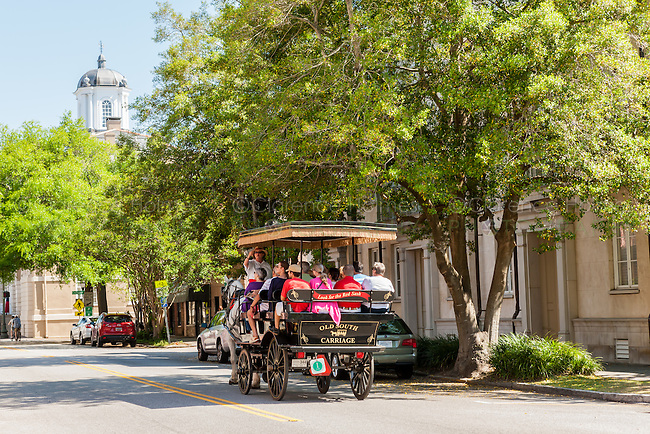 Tourists take a horse-drawn carriage tour on E Bay Street in historic Charleston, South Carolina.