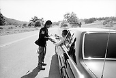 Santa Ynez Valley, California.USA.April 2005..A supporter and fan of pop singer Michael Jackson outside the gates of Mr. Jackson's Neverland ranch in Santa Ynez Valley runs after the car of Tito Jackson in hopes that the musician will sign his guitar. Tito stops his car and signs the instrument. The car is then surrounded by fans. The fans are there to support Michael Jackson in his child abuse trial. .Mr. Jackson, 46, denies all 10 charges against him, including child abuse. He faces up to 20 years in jail if convicted on all charges.