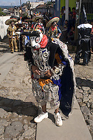 A participant in the Independence Day parade in Chichicastenango, Guatemala, wears an ornate bird costume and is let down only by his shoes.