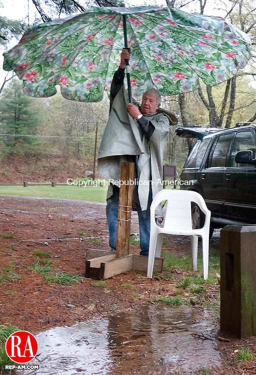 THOMASTON, CT. 28 April 2008-042808SV02--Bob Christian of Plymouth, known as &quot;Bluegill Bob&quot;, packs up his fishing umbrella after enduring heavy rain while fishing at Black Rock state park in Thomaston Monday.<br /> Steven Valenti Republican-American