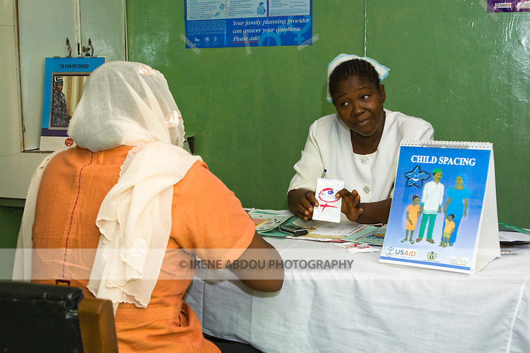 A U.S. Agency for International Development (USAID) employee talks to a health official at the Bukavu Barracks public clinic in Kano, Nigeria about female condoms.  A child spacing flipchart, designed by Nigeria's largest indigenous non-profit organization, the Society for Family Health, is prominently displayed on the desk.