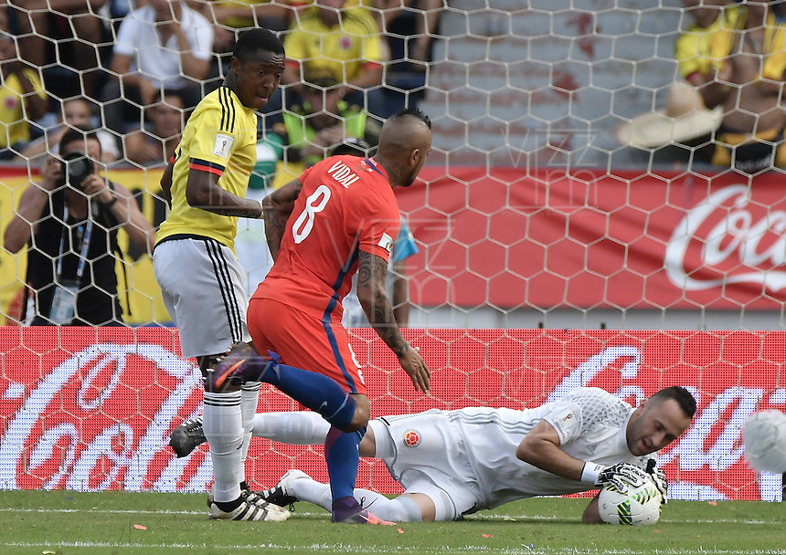 BARRANQUILLA - COLOMBIA - 10-11-2016:  David Ospina arquero de Colombia ataja el balón en frente  de Arturo Vidal (C) de Chile y Oscar Muilllo (Izq) de Colombia durante partido entre Colombia y Chile por la fecha 11 de la clasificatoria a la Copa Mundial de la FIFA Rusia 2018 jugado en el estadio Metropolitano Roberto Melendez en Barranquilla./ David Ospina, goalkeeper of Colombia, catchs the ball in front of Arturo Vidal (C) of Chile and Oscar Muilllo (L) during the match between Colombia and Chile for the date 11 of the qualifier to FIFA World Cup Russia 2018 played at Metropolitan stadium Roberto Melendez in Barranquilla. Photo: VizzorImage/ Gabriel Aponte / Staff