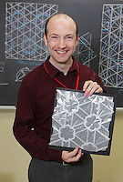 New York, NY, USA - June 25, 2011: Thomas Hull, Origami designer at the OrigamiUSA Convention in New York City holding one of his tessellations folded from one square of glassine without cuts.