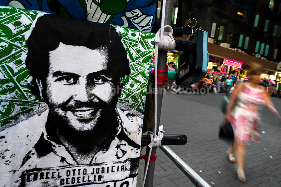 """A t-shirt for sale, depicting the drug lord Pablo Escobar, is seen arranged at the market stand on the street in Medellín, Colombia, 29 November 2017. Twenty five years after Pablo Escobar's death, the legacy of the Medellín Cartel leader is alive and flourishing. Although many Colombians who lived through the decades of drug wars, assassinations, kidnappings, reject Pablo Escobar's cult and his celebrity status, there is a significant number of Colombians who admire him, worshipping the questionable """"Robin Hood"""" image he had. Moreover, in the recent years, the popular """"Narcos"""" TV series has inspired thousands of tourists to visit Medellín, creating a booming business for many but causing a controversial rise of narco-tourism."""