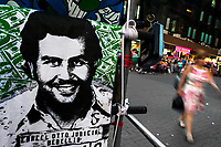 "A t-shirt for sale, depicting the drug lord Pablo Escobar, is seen arranged at the market stand on the street in Medellín, Colombia, 29 November 2017. Twenty five years after Pablo Escobar's death, the legacy of the Medellín Cartel leader is alive and flourishing. Although many Colombians who lived through the decades of drug wars, assassinations, kidnappings, reject Pablo Escobar's cult and his celebrity status, there is a significant number of Colombians who admire him, worshipping the questionable ""Robin Hood"" image he had. Moreover, in the recent years, the popular ""Narcos"" TV series has inspired thousands of tourists to visit Medellín, creating a booming business for many but causing a controversial rise of narco-tourism."