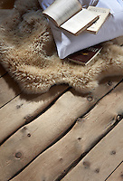 Books on a sheepskin rug lie on the worn original wooden floorboards of the chalet