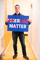 """John Paul Moran holds a banner he designed reading """"#HerLiesMatter,"""" in reference to Hillary Clinton, in his live/work studio in Boston, Massachusetts. Moran is a Trump supporter who will be traveling to Washington DC to attend the inauguration and associated events as Donald Trump is sworn in as president of the United States. Moran volunteered with the Trump campaign in Massachusetts and helped organize rallies around his """"#HerLiesMatter"""" campaign."""