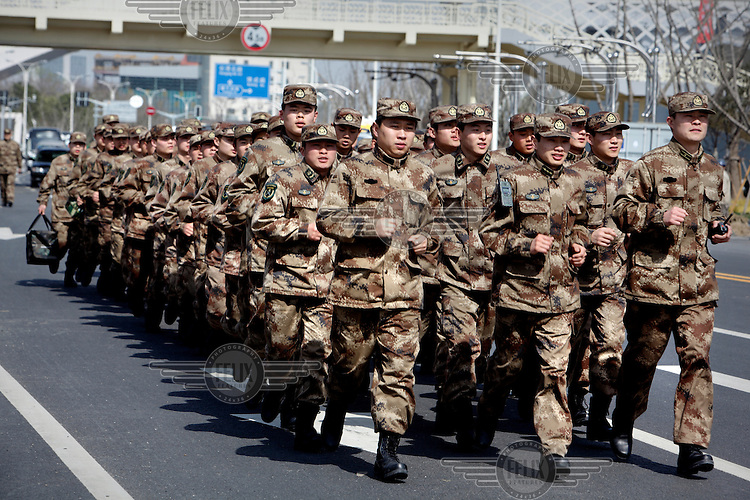 Chinese People's Liberation Army soldiers run, in file, through the grounds of the 2010 World Expo site.