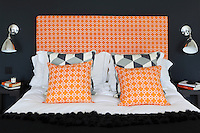 A bed dressed with bright orange cushions and a matching upholstered headboard