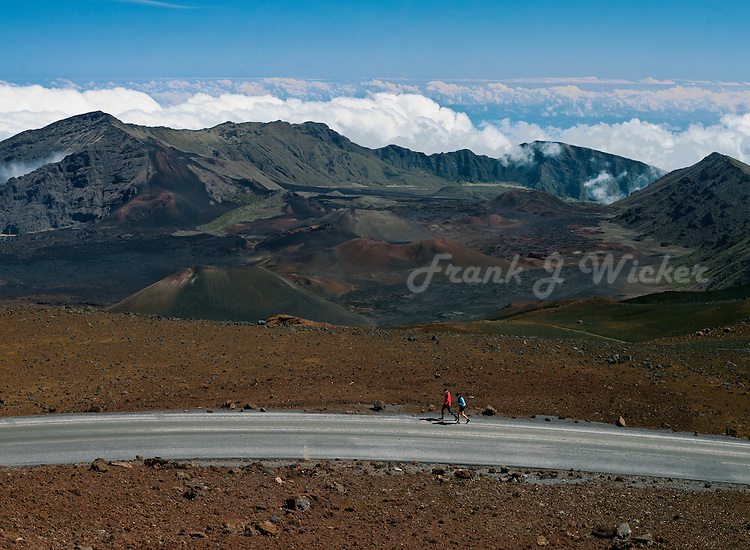 High above the clouds at the 10,000 foot level in HALEAKALA NATIONAL PARK on Maui in Hawaii these runners are satisfying their test of endurance
