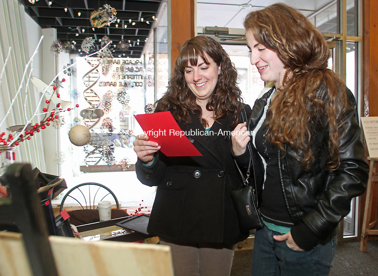 Torrington, CT-121413MK41 (from left) Whitney Galgano and Kelsey Ocain, both from Bantam, look at a sample of work from Rachel Saloio from RachelsPaintings.com during the Torrington's Makers Market on Water Street Saturday afternoon. Saloio specializes in chalkboard creations for local businesses. The event, curated, organized, and hosted by Sarah Galgano of MilliMari Modern said that nine of the fifteen artisans from across New England and the Tri-State area were able to show their work as weather impacted travel for the other artists.  Galgano is looking forward to making this an annual event.  Michael Kabelka Republican-American