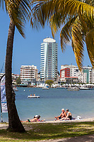 Fort-de-France, Martinique.  Two Couples Relaxing on the Beach.  Pointe Simon Business Center across the Water.