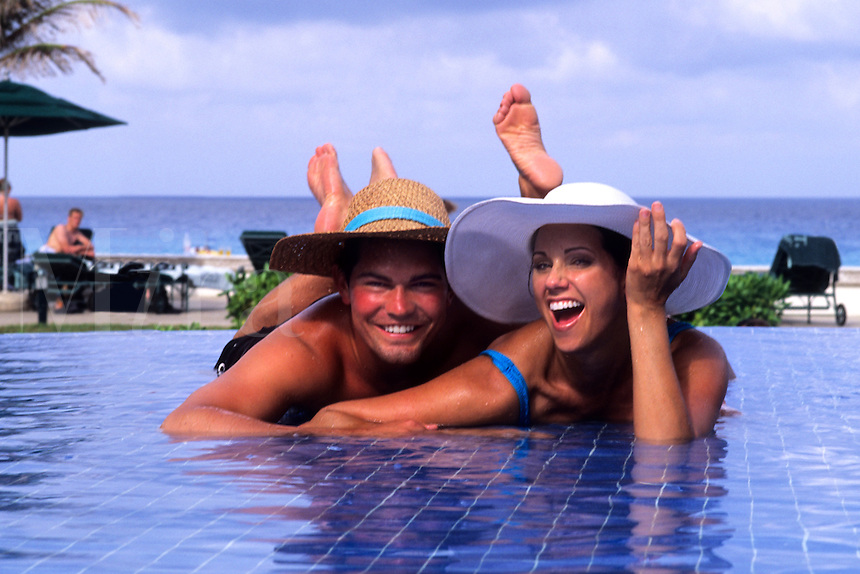 Young tourists age 20s relaxing by tile pool in Cancun Mexico.