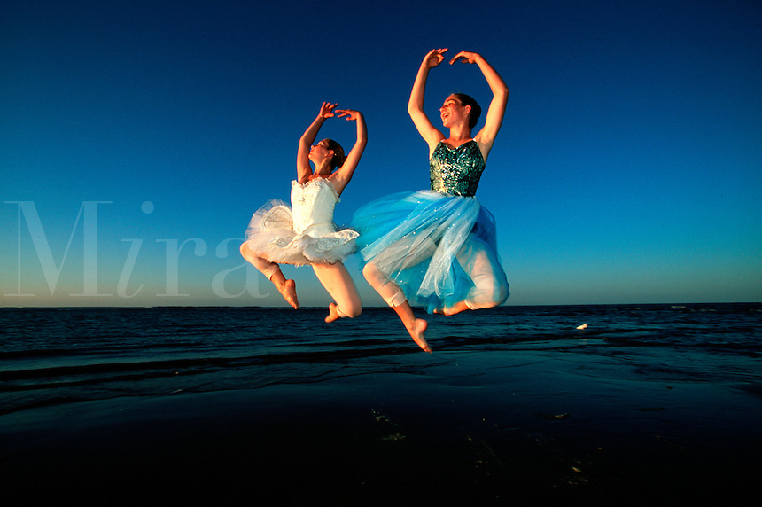 Ballet dancers jumping in unison during sunset dance at the beach.