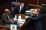 Nevada Sens. Kelvin Atkinson, left, and Ruben Kihuen, center, talk with Lt. Gov. Mark Hutchison on the Senate floor at the Legislative Building in Carson City, Nev., on Wednesday, April 8, 2015.  <br /> Photo by Cathleen Allison