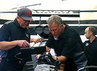 Apr 25, 2015; Baytown, TX, USA; Team owner Alan Johnson (left) and crew chief Brian Husen make adjustments to the dragster of NHRA top fuel driver Shawn Langdon during qualifying for the Spring Nationals at Royal Purple Raceway. Mandatory Credit: Mark J. Rebilas-