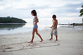 FRENCH POLYNESIA, Moorea. Fiona and Dushan playing at a local beach at dusk.