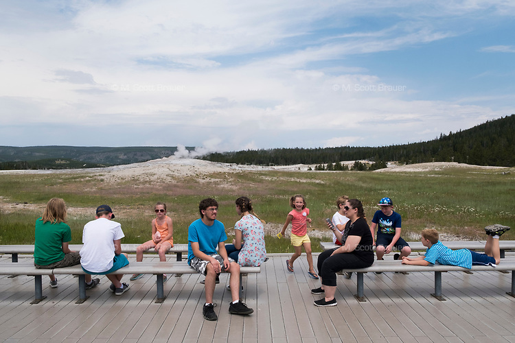 People sit on the boardwalk next to Old Faithful after the geyser erupted in Yellowstone National Park, Wyoming, USA. In the days surrounding when this image was taken, the geyser averaged an eruption about every 90 minutes, though occasionally there were hours between eruptions.