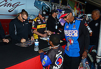 Oct. 27, 2012; Las Vegas, NV, USA: NHRA top fuel driver Brandon Bernstein gives an autograph to an Antron Brown fan during qualifying for the Big O Tires Nationals at The Strip in Las Vegas. Mandatory Credit: Mark J. Rebilas-