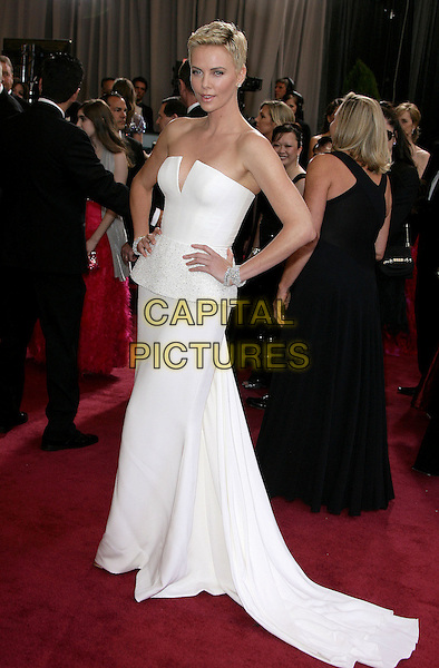 Charlize Theron (wearing Dior Couture).85th Annual Academy Awards held at the Dolby Theatre at Hollywood & Highland Center, Hollywood, California, USA..February 24th, 2013.oscars full length dress white strapless peplum short cropped hair pixie cut hands on hips train .CAP/ADM.©AdMedia/Capital Pictures.