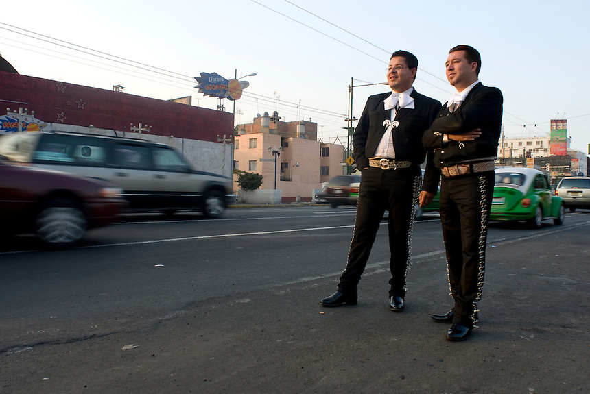 Two Mariachis try to flag down prospective clients in traffic just outside Plaza Garibaldi where Mariachis gather to be hired in Mexico City, Friday, Jan. 4, 2008