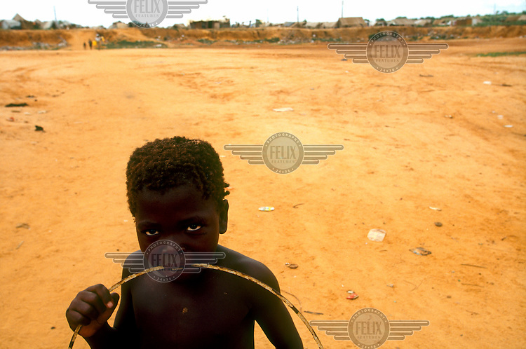 A child in an area of unused land in a camp for internally displaced persons (IDPs) on the outskirts of Luanda.