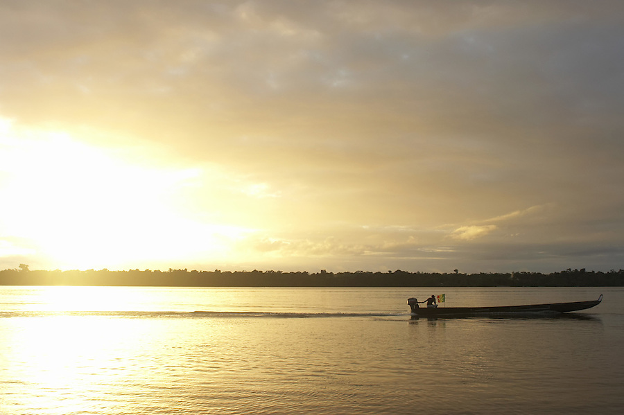 Dugout canoe traveling up the Marowijne River at sunset near the village of Bigiston, Suriname.