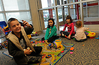 STAFF PHOTO FLIP PUTTHOFF<br /> KIDS AT PLAY<br /> Mason Gartrell, left, and Jenna Mondagon, second from left, play with dinosaurs Wednesday Dec. 31 2014 during KIDcare at the Rogers Activity Center. The center now charges a fee for child care. Vilana LaPlant, right, and Sophia LaPlant, second from right, play with toys during KIDcare.